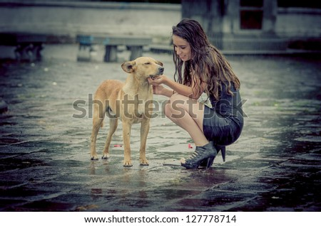 Girl comforting a with dog under rain.