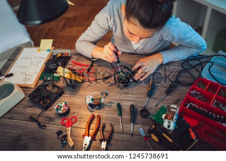 Girl constructs technical toy. Technical toy on table full of details #1245738691