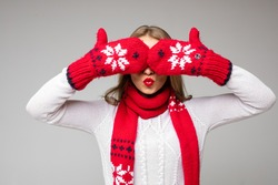 Girl covering eyes with winter mittens. Isolate on grey.