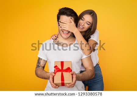Photo of  Girl covering her boyfriend eyes and giving him present on yellow background