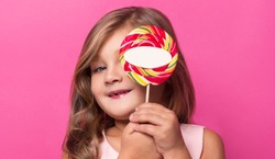 girl covers her face with candy and smiles