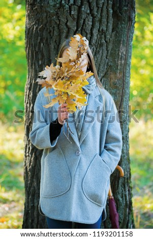 girl covers her face with oak branches. Woman covers her face with dry yellow oak leaf in autumn forest. autumn portrait in the park. girl in a gray coat. a red umbrella stands by a big oak #1193201158