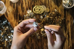 Girl craftsman dismantles clock shoot close up. Female hands holding tweezers. Repairing vintage watches. Disassembly of clock on background of wooden table. Watchmaker with pincers  in soft focus.