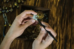 Girl craftsman dismantles watch. Beautiful female fingers with forceps at work. Female hands holding tweezers. Repairing vintage clock. Disassembly of clock on background of wooden table.