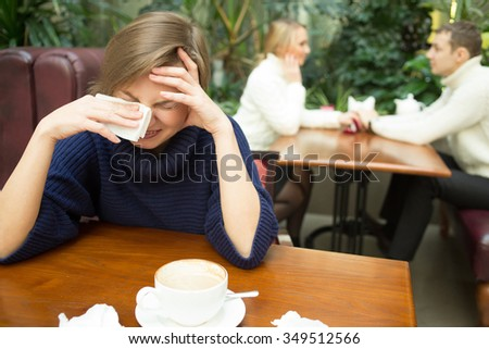 girl crying on background happy couple. sitting in cafe