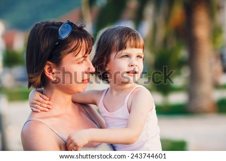 Girl cuddling mother. Little cute girl in mother\'s arms during summer holiday walk - selective focus (girl\'s eyes perfectly sharp - mother face is slightly out of focus) -very shallow depth of field