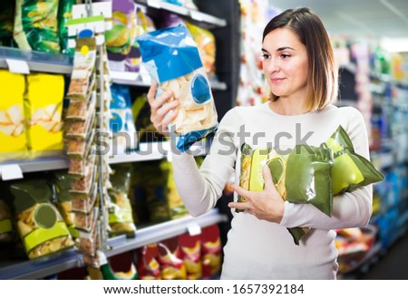 Girl customer looking for tasty snacks from shelves in supermarket