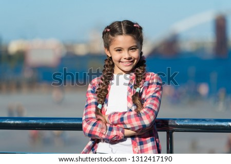 Girl cute kid with braids relaxing urban background defocused. Organize activities for teenagers. Vacation and leisure. What do on holidays. Sunny day walk. Leisure options. Free time and leisure.