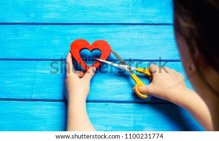 girl cuts the heart with scissors, the concept of breaking relations, quarrels and divorce. Betrayal of the othere. blue background