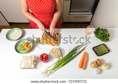Girl cutting carrots and preparing food #725900731