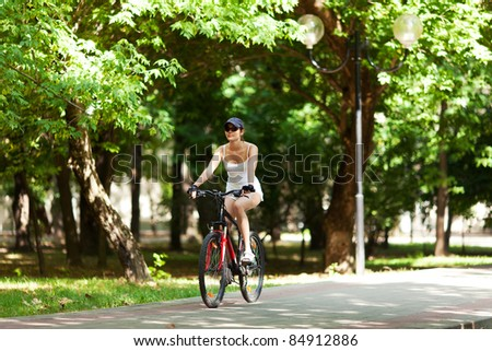 Girl cycling in the park. She's wearing white sport clothes, cap, her bicycle is red. It's a sunny summer day.