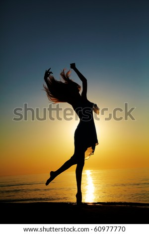 Girl dances on the beach at sunset. Natural light and darknesss. Artistic colors added. Vertical photo