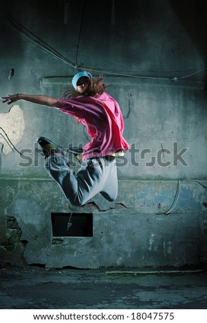 Girl dancing on a street next to old grungy wall