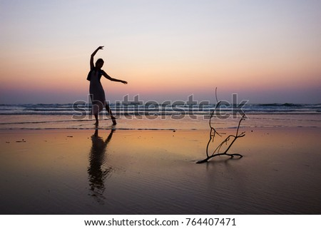 Stock Photo girl dancing on the beach, silhouette