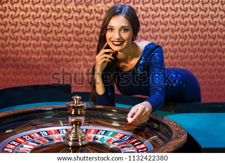 Girl dealer spin the spinner. Dealer in the casino behind the roulette table