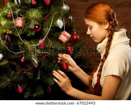 girl decorate the Christmas tree in a house interior