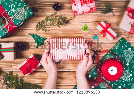Girl decorates a Christmas gift box with a wooden desk #1213896133