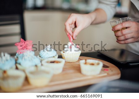 Girl decorates cupcakes #665169091