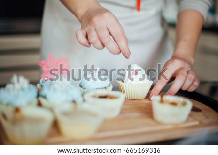 Girl decorates cupcakes #665169316