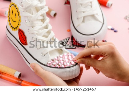 Girl decorates her favorite white sneakers with patches and rhinestones. Handmade, custom design for shoes, DIY concept.