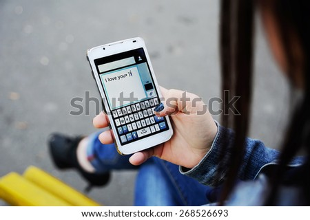 Girl dials sms message on mobile phone