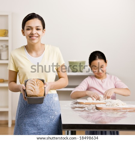 Girl displays baked loaf of bread while sister kneads dough