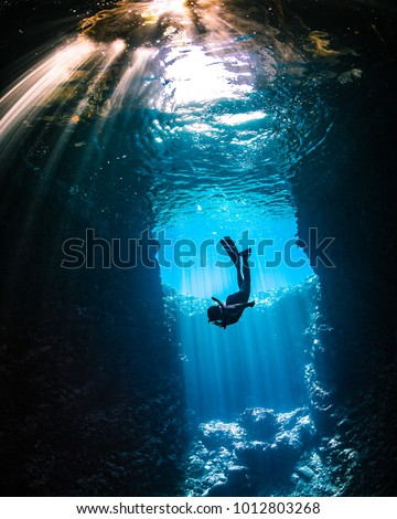 Stock Photo Girl diving in cavern with lightbeams coming on top of her