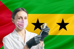 Girl doctor prepares vaccination against the background of the Sao Tome and Principe flag. Vaccination concept Sao Tome and Principe.