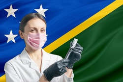 Girl doctor prepares vaccination against the background of the Solomon Islands flag. Vaccination concept Solomon Islands.