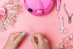 Girl does manicure at home on pink background, view above
