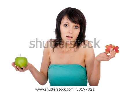 Girl does not know what to eat - apple or cookies.