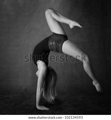 Girl doing back bend or gymnastics in black and white