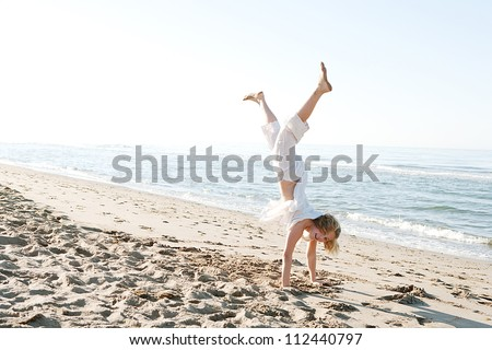 Girl doing cartwheels on a golden sand beach near the shore, smiling happy.