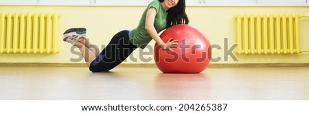 girl doing crunches in the gym.  cute sexy fitness girl in gym dress based on red rubber ball near yellow wall and window Beautiful latin hispanic woman laying on the splits Copy space for inscription
