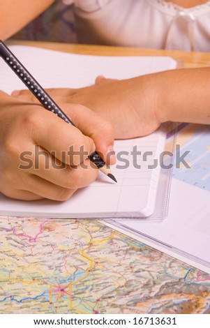 Girl doing her homework by writing in notebook.