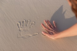 girl doing imprint with the hand in white sand