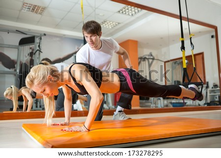 Stock Photo girl doing pushups with resistance band in the presence of a personal trainer