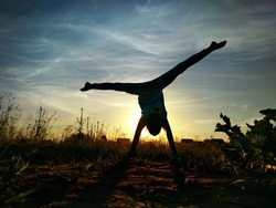 Girl doing split on handstand. A model stands on her hands, doing gymnastic splits against the blue sky. Healthy lifestyle concept. Silhouette on sunset background. Gymnastic in nature