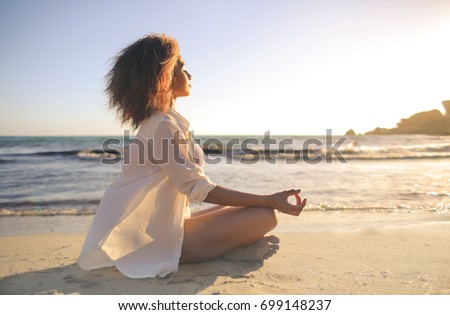 Girl doing yoga at the beach, at sunset time #699148237