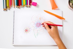 Girl drawing a colorful flower first person view