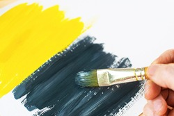 Girl draws abstract gouache painting yellow and gray colors. Brushstrokes on canvas. Color 2021.
