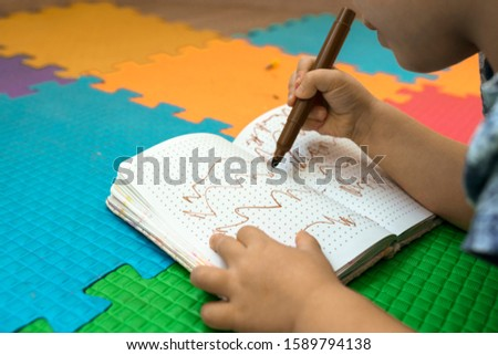 girl draws with felt-tip pens on a colored background. brown drawing on a white sheet. children's creativity