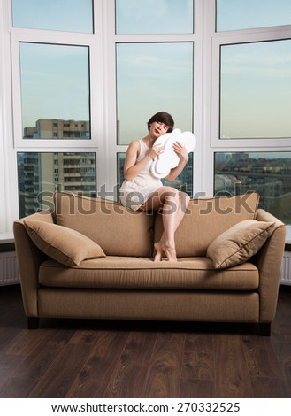 Girl dreaming with a white cloud on a couch