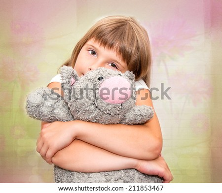 Girl dreaming with grey plush toy cat