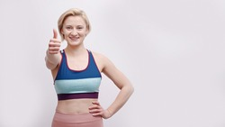 Girl dressed in activewear making thumbs-up sign at the camera. Strong girl posing for the camera showing her strength. Concept of fitness and gym. Isolated over white background studio.
