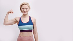 Girl dressed in activewear showing her biceps. Strong girl posing for the camera showing her muscles and strength. Concept of fitness and gym. Isolated over white background studio.