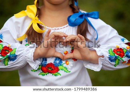Girl dressed in vyshyvvanka making heart sign with hands.  Her hair is woven with ribbons in the colors of the national flag - yellow and blue. Ukrainian Vyshyvanka`s day. Independence Day of Ukraine Foto d'archivio ©