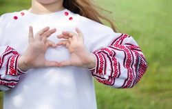 Girl dressed in vyshyvvanka making heart sign with hands. Traditional, ethnic, prints and ornaments. Vyshyvanka.Ukraine. Ukrainian Vyshyvanka`s day.Independence Day of Ukraine.