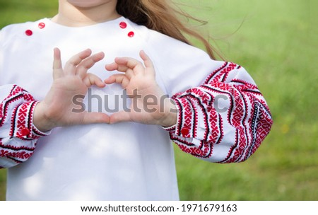 Girl dressed in vyshyvvanka making heart sign with hands. Traditional, ethnic, prints and ornaments. Vyshyvanka.Ukraine. Ukrainian Vyshyvanka`s day.Independence Day of Ukraine. Сток-фото ©
