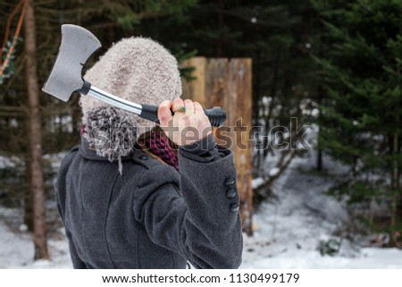Girl dressed in winter clothes holds an axe in front of a wooden board as part of an axe throwing competition